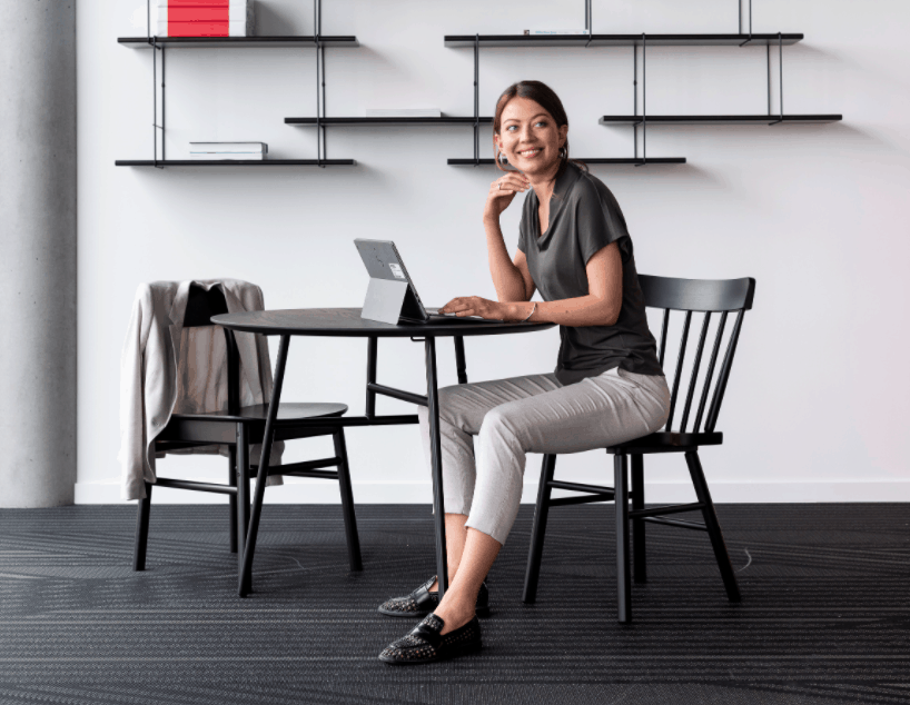Women sits on a table at home to book a free desk at the smart office Building IoT automation creates cost-effective facilities