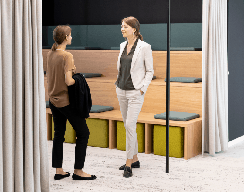 Two women talk to each other in the smart office after they coordinated an appointment through the workplace app Building IoT automation creates cost-effective facilities